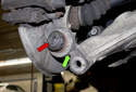 While holding the control arm down, align the rear ear of the control arm with the ball joint bore (green arrow).