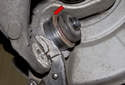 Install the new ball joint into the mounting bore so the retaining lip (red arrow) faces the front of the vehicle.