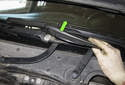 Right wiper blade adjusting: Working at the right side wiper arm, remove the plastic cover by pulling it away from the arm toward the left and then straight up (green arrow).