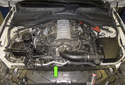 The thermostat is located at the front of the engine, just below the coolant pump (green arrow).