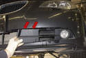 Working at the corner of the bumper, unclip the top (red arrows) of the fog light trim piece.