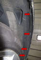 Working in the rear of the fender well, remove the four 8mm fasteners from the wheel well liner (red arrows).