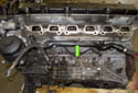 With the intake manifold removed, you now have to remove the coolant pipe (green arrow) from the crankcase.