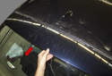 Slide the spoiler toward the rear bumper about two inches to detach the mounts (red arrow).