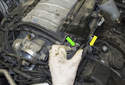 Working at the left side of the intake manifold, pull the electrical connector (green arrow) straight out of the electrical junction.
