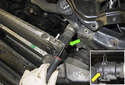 Working at the upper radiator hose, use a flathead screwdriver to lever out the coolant hose retaining clip (green arrow).