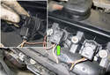 Unlock the ignition coil electrical connector (green arrow) by pulling the tab up 90°.