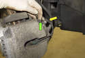 Open the brake caliper bleeder cover (green arrow) and remove the pad wear sensor (yellow arrow) wire from the mount.