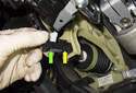 Remove the brake light switch by sliding it (green arrow) out of the mounting bracket toward the rear of the vehicle.