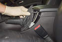 Working in the vehicle interior, lever the top of the parking brake lever boot out using a plastic prying tool.