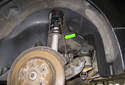 Remove the brake caliper with the bracket from the wheel carrier and hang it using a piece of metal coat hanger or a strong bungee cord (green arrow).