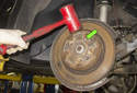 Next, using a 6mm Allen bit, remove the brake rotor-mounting fastener (green arrow).