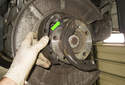 Then remove both parking brake shoes together with the spring (green arrow).