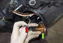 Front Driving Light: Disconnect the electrical connector (red arrow) from the bulb (green arrow) and install a new bulb.