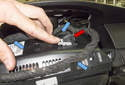Next, press the small button and rotate the connector lock 90° to disconnect the connector (red arrow).