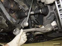 Then, pull the lower control arm out of the subframe and allow it to hang.