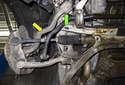 The front tension strut (yellow arrow) connects to the steering knuckle via a ball joint and to the subframe via a bushing (green arrow).