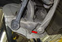Working at the steering knuckle, remove the 21mm ball joint nut (red arrow).