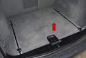 The battery in BMW X3 models is located in the right side of the luggage compartment, under the carpet trim (red arrow).