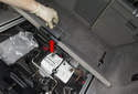 Working in trunk, lift and fold up the carpet panel (red arrow).