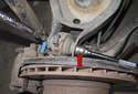 Remove rear ball joint 18mm fastener (red arrow).