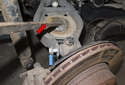 Next, lever upper control arm (red arrow) at angle and remove bolt (blue arrow).