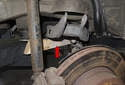 Placing a block of wood (red arrow) between the trailing arm and the axle for easier access.