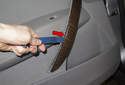 Using a plastic prying tool, lever the door handle trim piece off the door panel (red arrows).