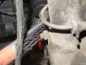 If the strut is covered in debris, start by brushing it off and cleaning the strut fastener threads (red arrow).