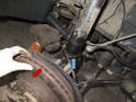 Pull the wheel bearing carrier (red arrow) away from the strut (blue arrow).