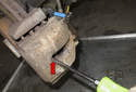 Place a drain pan under the caliper.