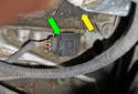 The crankshaft position sensor (green arrow) is located near (below) the starter motor (yellow arrow), mounted in the engine block (crankcase).