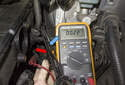 Testing with sensor removed: In this photo the wrench (blue arrow) is close to the sensor (red arrow), so the DVOM reads 0.