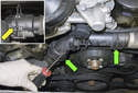 Working at both radiator hoses, use a flathead screwdriver to lever out the coolant hose retaining clips (green arrows).