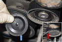 Locate the accessory drive belt idler pulley and remove the dust cap (blue arrow) using a flathead screwdriver (red arrow).