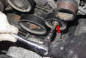 Then remove the T45 Torx idler pulley (red arrow) bolt.