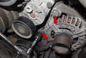 Working at the front of the alternator, remove the 16mm alternator mounting bolts (red arrows).