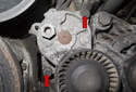 Accessory belt tensioner: Using a 13mm socket, remove the two tensioner fasteners (red arrows).