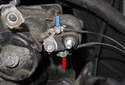 Working at the starter solenoid, remove the 8mm nut (blue arrow) and 10mm nut (red arrow).