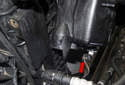 Working at the bottom of the coolant tank, disconnect the coolant level sensor electrical connector by pressing the tab (red arrow) and pulling the connector straight off.