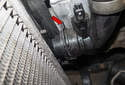 Working at the lower radiator hose, use a flathead screwdriver to lift the hose spring locks (red arrow) up until they stop.