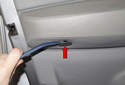 Using a plastic prying tool to lever the trim cap out at the end of the arm rest (red arrow).