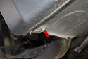 Rear liner: Working at the front bottom of the rear wheel well liner, remove the 8mm fastener (red arrow).