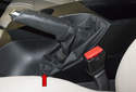 Working in the vehicle interior, lever the bottom (red arrow) of the parking brake lever boot out using a plastic prying tool.