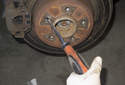 Using a long, thin flathead screwdriver, rotate the adjuster to retract the parking brake shoes until the wheel spins free.