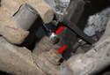 Working behind brake caliper: Remove two 16mm brake caliper bracket mounting bolts (red arrows).