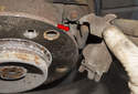 Check that the parking brake lever is correctly hooked to the parking brake cable (red arrow) before installing the brake shoes.