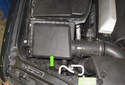 The engine air filter is located on the right side of the engine compartment, near the radiator support (green arrow).