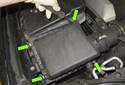 Then, using a flat head screwdriver, open the four-air filter lid retaining clips (green arrows).