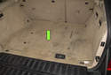 The battery in BMW E53 X5 models is located in the center of the luggage compartment, below the spare tire (green arrow).